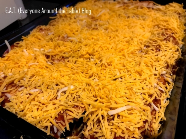 Chicken Enchiritos sprinkled with cheese before baking.